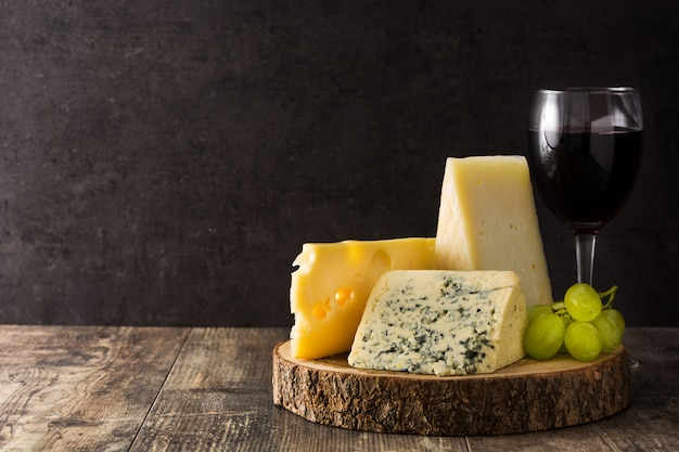 チーズと木製のテーブルの上のワインの品揃え。 Premium写真