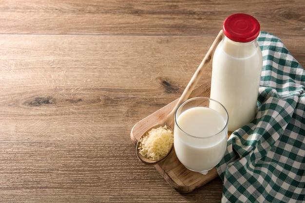 Рисовое молоко в стакан и бутылка на деревянный стол Premium Фотографии