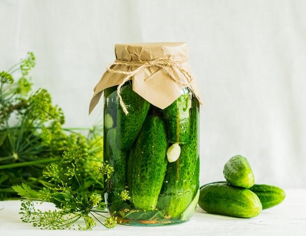 テーブルの上のガラスの瓶に発酵または缶詰のキュウリ秋の収穫の処理。缶詰食品 Premium写真