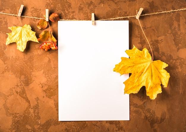 茶色の洗濯はさみに紙と乾燥した葉の空の白いシートが掛かる Premium写真
