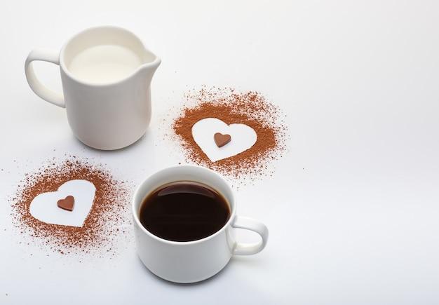 Две формы сердца из порошка какао, чашка кофе с молоком и копией пространства на белом фоне Premium Фотографии