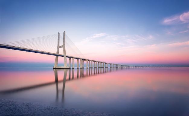ポルトガル、リスボン-日没でリスボンのバスコダガマ橋。ヨーロッパ。長時間露光写真 Premium写真