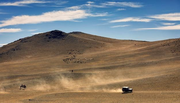 車が道路を運転しています。ほこりが多い。山の近くの砂漠で羊や山羊の群れが放牧します。モンゴル。アルタイ山脈。アジア Premium写真