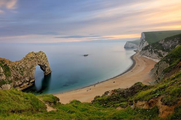 Природный известняк арка дурдл дверь на юрском побережье дорсет в англии на закате Premium Фотографии