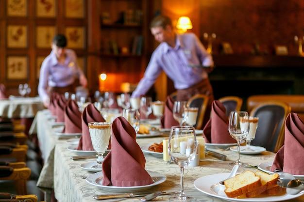 Официанты накрывают на стол Premium Фотографии