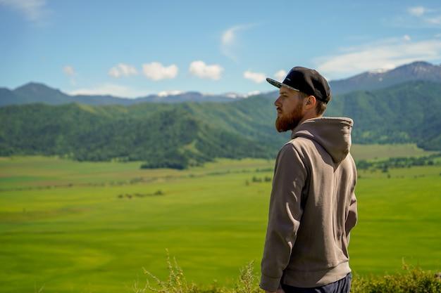 緑の野原と山の前にフーディ立って赤ひげを生やした男 Premium写真