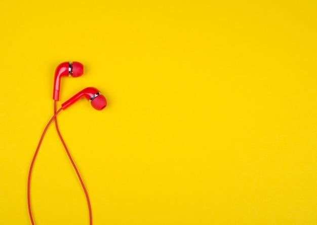 Красные наушники-вкладыши на ярко-желтом фоне Premium Фотографии