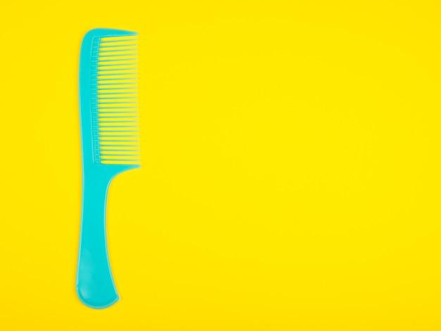 Синяя расческа для волос на ярко-желтом фоне Premium Фотографии