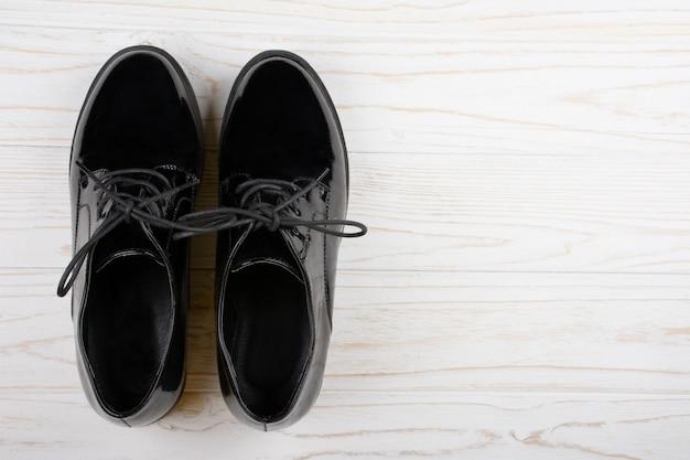 Черные лакированные туфли на белом фоне деревянные Premium Фотографии
