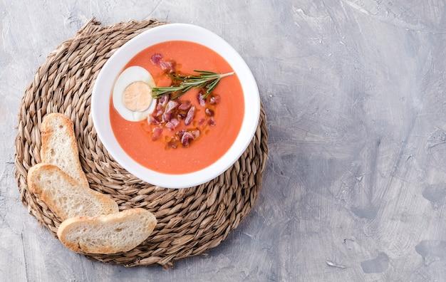 サルモレホスープ、スペインの伝統料理。ボウルにハムと卵を入れて Premium写真