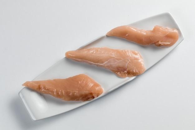 モダンな白いプレートに鶏の胸肉生 Premium写真