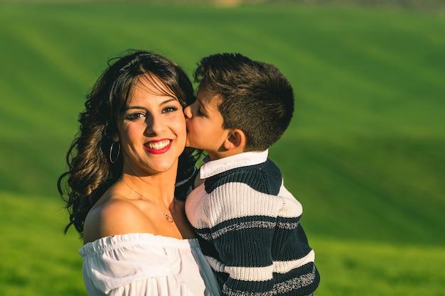 Женщина и мальчик на природе на фоне летнего поля. позы на природе Premium Фотографии