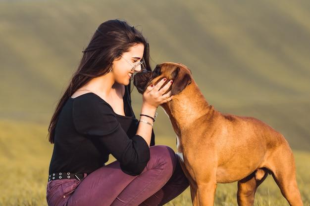 秋の牧草地で彼女のボクサー犬とファッションの女の子 Premium写真