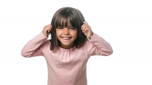 白い背景の上のカメラに舌を見せて面白い少女 Premium写真
