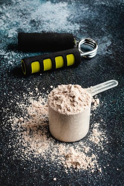 トレーニングを開始するためのフィットネス栄養のためのタンパク質粉末で満たされたスクープ Premium写真