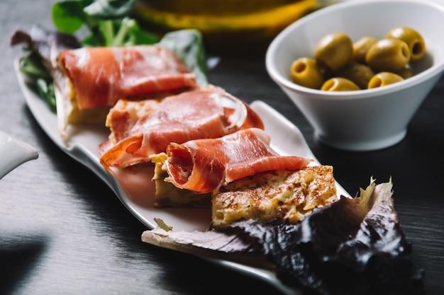 セラーノハムとオリーブのおいしいスペイン風ポテトオムレツ Premium写真