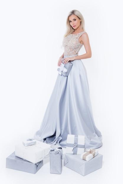 分離した白い背景でギフトボックスと長い銀のドレスで幸せな笑顔金髪女 Premium写真