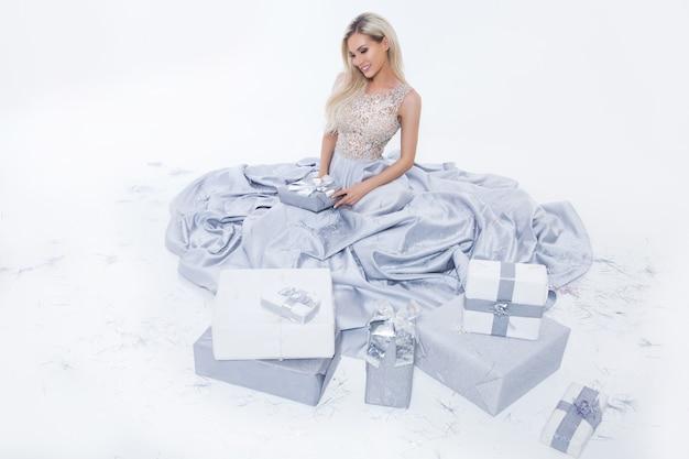 Счастливая усмехаясь белокурая женщина в длинном серебряном платье с подарочной коробкой и падая конфетти на белой изолированной предпосылке Premium Фотографии