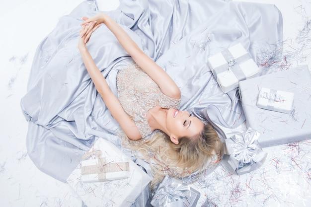 ギフト用の箱と落ちてくる紙吹雪と長い銀のドレスで幸せな笑顔金髪女 Premium写真