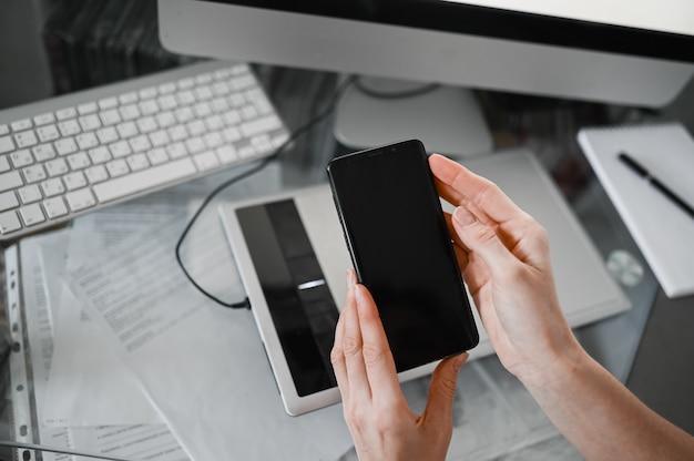 インテリア職場でスマートフォンを使用して女性の手、オフィスデスクで携帯電話を使用してフリーランスのビジネス女性、スマートフォンとノートブックコンピューターを使用して自宅から作業します。リモートワーカー検疫 Premium写真