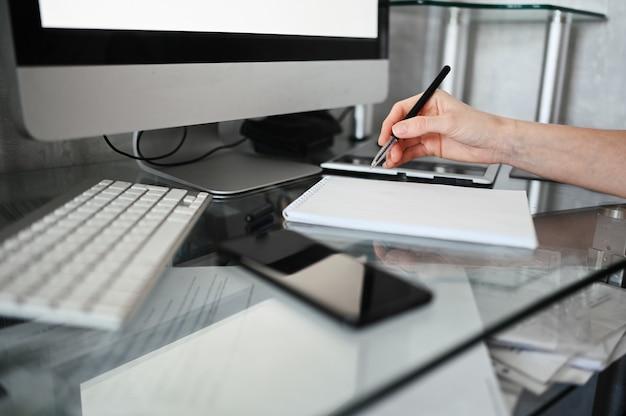 認識できない女性の手が空のノートブックとコンピューターに書き込みます。検疫中に自宅でスマートフォンとラップトップを使用するフリーランサー。インターネットマーケティング、金融、ビジネス、リモート作業の概念 Premium写真