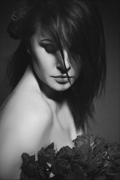 小さな赤いバラと若い美しいブルネットの肖像画 Premium写真