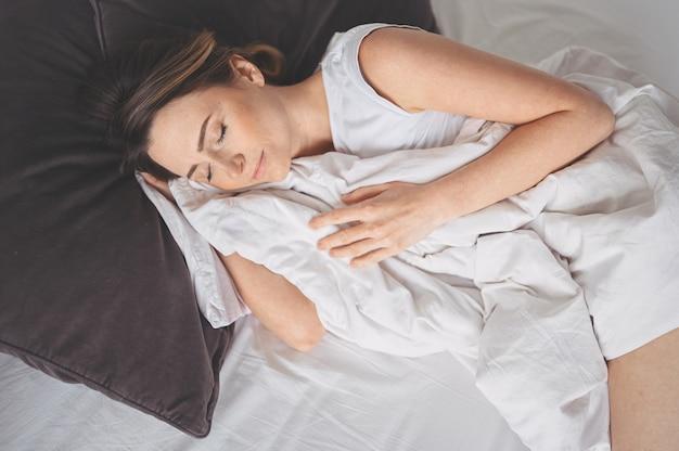Привлекательная улыбающаяся молодая женщина, растягивающаяся в постели, просыпающаяся одна счастливая концепция, бодрствующая после здорового сна в удобной удобной кровати, и матрас наслаждаются добрым утром Premium Фотографии