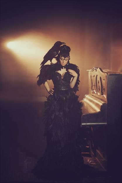 Фасонируйте готический портрет красивой брюнетки с вороной в длинном черном платье из вороньих перьев. хэллоуин Premium Фотографии