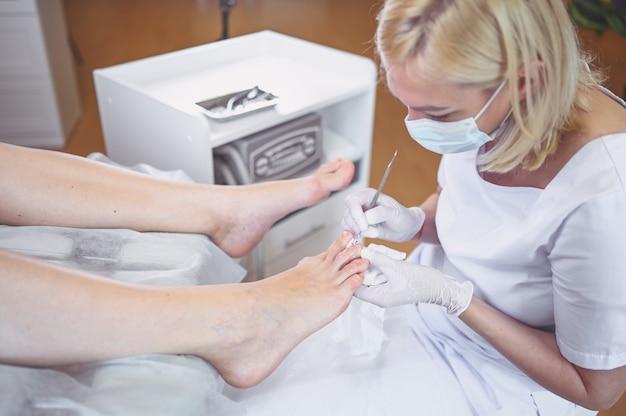 二重の爪の器具を使用してプロの医療ペディキュアの手順をクローズアップ Premium写真