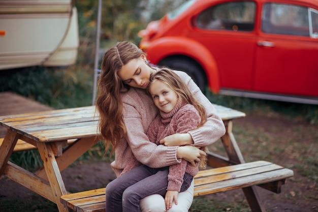 母と幼い娘を抱き締めると赤いレトロな車でキャンピングカーの休暇に田舎でリラックスの肖像画 Premium写真