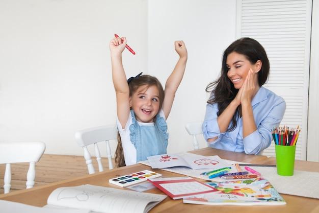 笑顔の母と娘は学校の準備をしており、鉛筆と絵の具で描くことに取り組んでいます Premium写真
