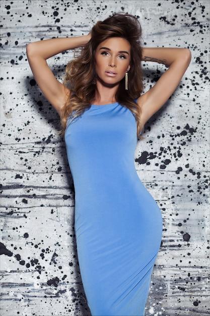 薄茶色の髪、ファッションメイクアップ、髪型、青いフィッティングイブニングドレスでポーズ美しいエレガントな若い女性 Premium写真