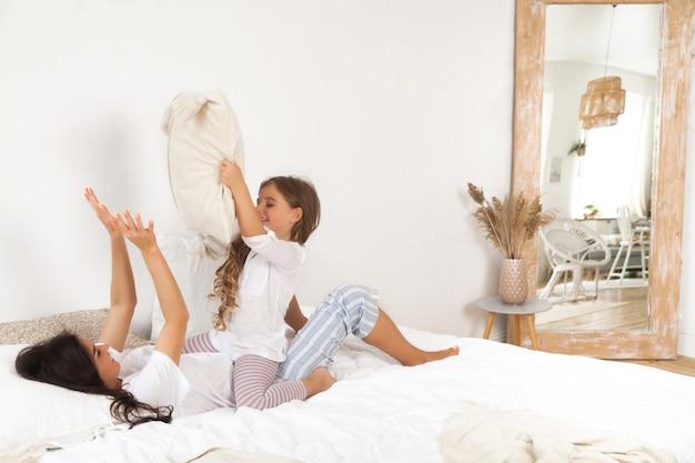 母と娘が遊んで、朝早くベッドで楽しんで笑顔 Premium写真