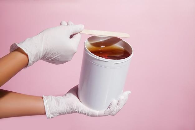 Концепция депиляции и удаления волос. закройте вверх руки доктора в перчатках и медицинской форме халата с сахарной пастой Premium Фотографии