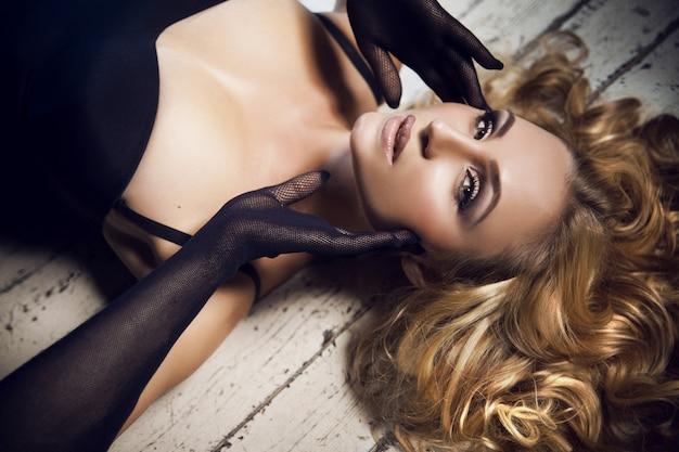 ファッションメイクと黒のボディースーツと白い木の床でポーズをとって網手袋で巻き毛のヘアスタイルと美しい官能的な豪華な若いブロンドの女性の肖像画間近します。 Premium写真