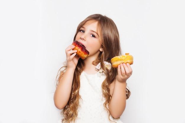 ドーナツでポーズをとって興奮した少女 Premium写真