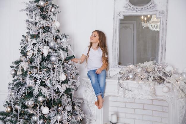 ミラー付きの暖炉の上に座って白のクラシックなインテリアでクリスマスツリーを飾る小さな女の子子供。メリークリスマス、新年あけましておめでとうございます、幸せな休日。 Premium写真