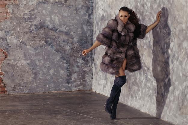 冬のファッションスタイル。膝のブーツで裸の体に高級毛皮のコートで美しい女性。 Premium写真