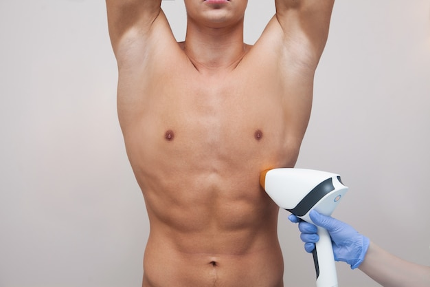 Мускулистый мужчина спортсмен, подняв руки и показывая подмышки, подмышки гладкой чистой кожи. эпиляция и депиляция волос в салоне красоты. мужская лазерная эпиляция Premium Фотографии