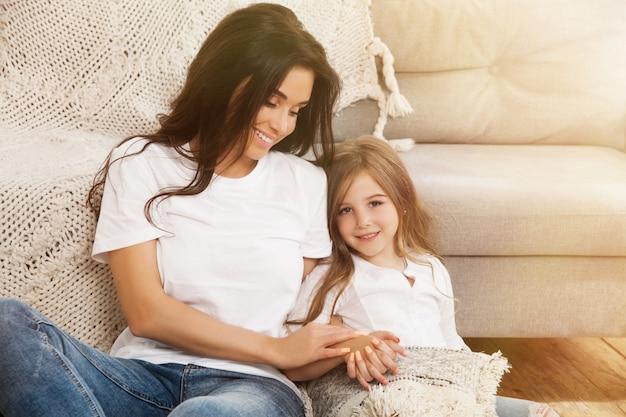 Привлекательная молодая женщина с маленькой милой девушкой проводят время вместе дома Premium Фотографии