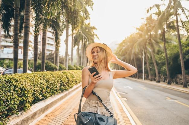 アジアの休暇観光の街を歩く中国人観光客。バックパック、スマートフォンで白人美人。旅行ライフスタイルコンセプト。海南省三亜の緑のヤシと高速道路の通り。 Premium写真