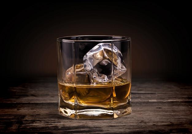 木材の背景にウイスキーのグラス。 Premium写真