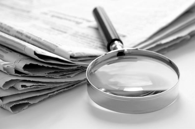 ニュースを見つけるための日刊紙と虫眼鏡 Premium写真