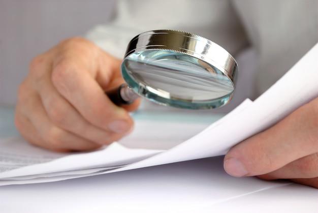 Бизнесмен, глядя через увеличительное стекло на документы Premium Фотографии