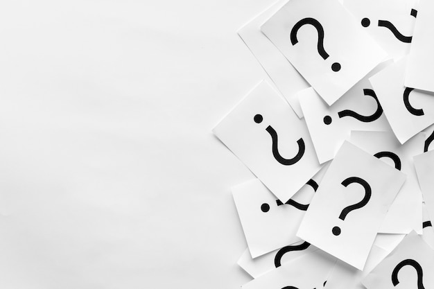 Куча вопросительных знаков напечатана на белых карточках Premium Фотографии