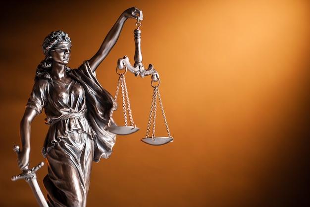 Бронзовая статуя правосудия держит весы Premium Фотографии