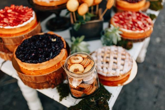 秋の結婚式の甘いバー。ケーキ、カップケーキ、甘さと花。 Premium写真