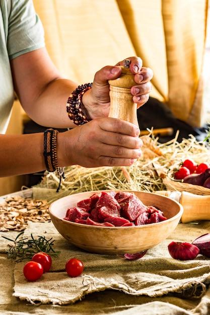 Добавить перец к говядине с мельницей в руках шеф-повара, яркая рамка. восточно-азиатская кухня. рецепт еды, фото, копия текста Premium Фотографии
