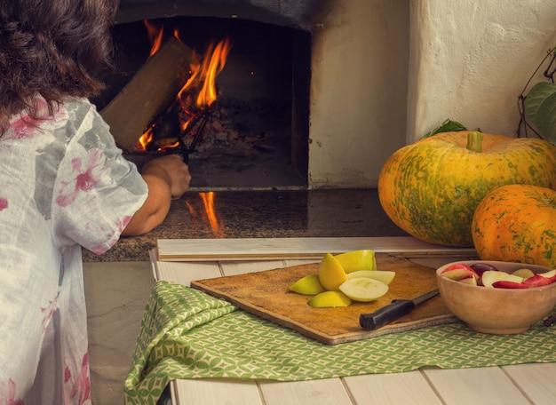 女性はオーブンで火を燃やす Premium写真