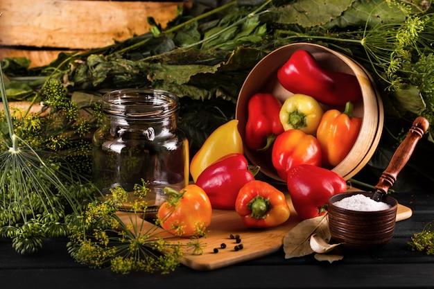 野菜の保存。テーブルの上には、唐辛子、玉ねぎ、ニンニク、塩入れがあります。 Premium写真